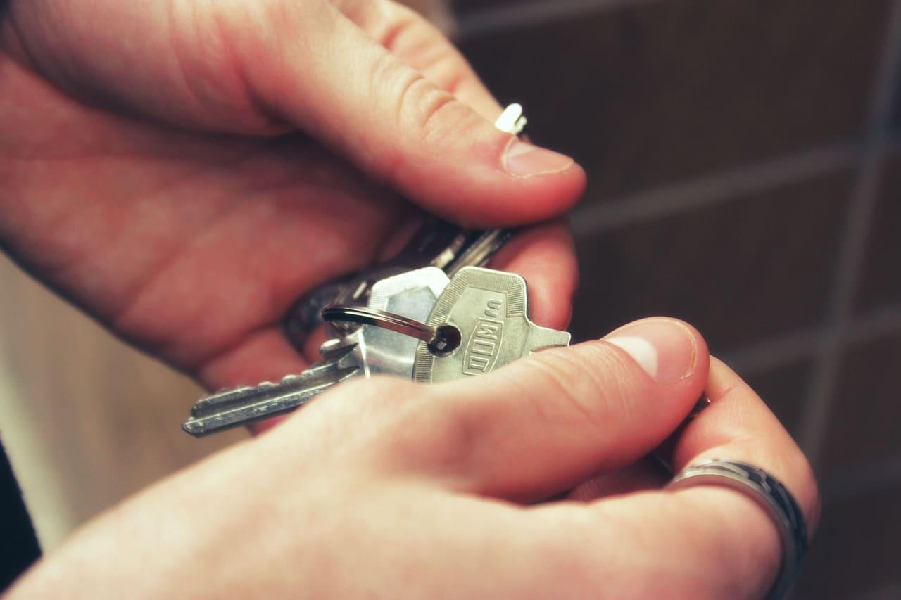 Hand holding keys to house door